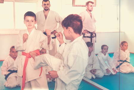 Two young boys training in sparring to use new technique at karate class