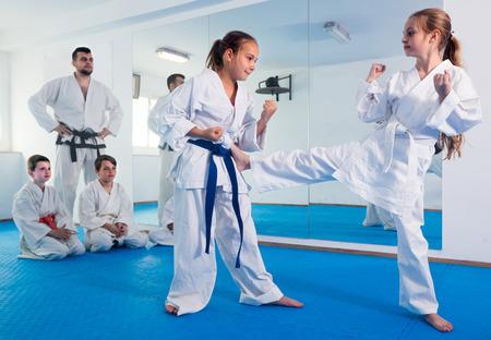 若い女性は空手クラスで新しい動きを使用するスパーリングでしようとしています。