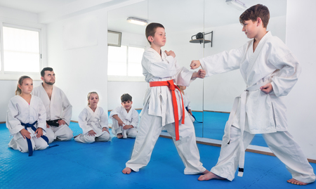Pair of little boys practicing new karate moves during a class