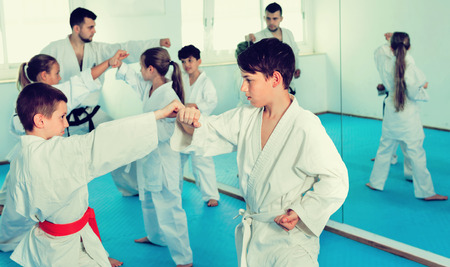 Diligent  teenagers practicing new karate moves in pairs in class