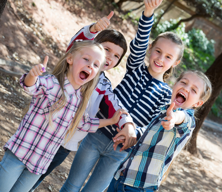 Group of excited cheerful  little friends with thumbs up together in city park. Selective focus Stock Photo