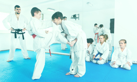 Pair of little boys practicing new karate moves during class in a gym