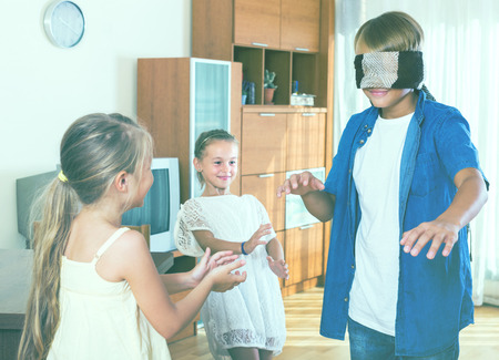 blind child: Blindfolded boy catching cheerful little sisters playing in Kagome at home