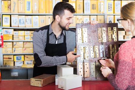 Seller offering door hinges to female customer in houseware shop Stock Photo