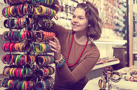 clasps: Smiling young female showing different bracelets in the market Stock Photo