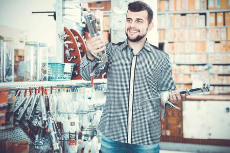 smiling male customer examining various glue guns in houseware store