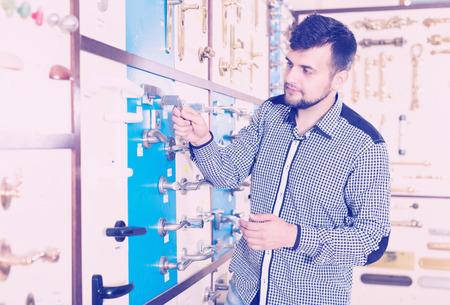 Smiling man choosing new door handle in houseware store