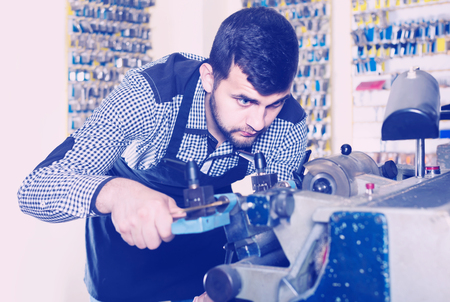 specialized job: positive male worker shaping new key in repair workshop Stock Photo