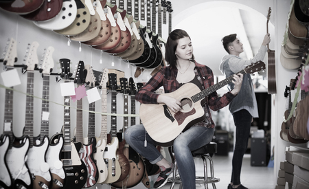 suitable: Smiling italian teenage customers deciding on suitable acoustic guitar in guitar shop