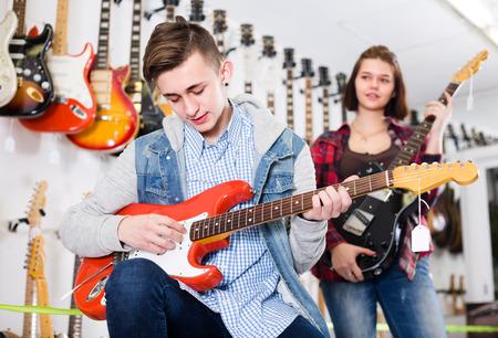 적합: Young musicians are deciding on suitable amp in guitar shop. 스톡 콘텐츠