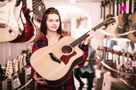 Female teenager examining various acoustic guitars in guitar shop Stock Photo
