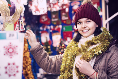 Cheerful positive teenage girl shopping at festive fair before Xmas Stock Photo