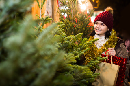 overspending: Happy adult girl staying at market among Christmas trees