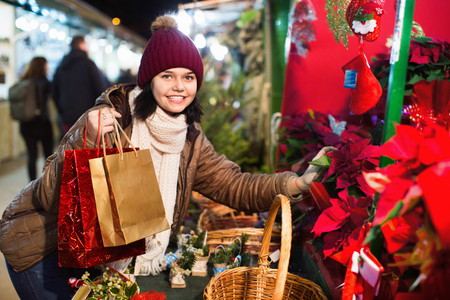overspending: Young happy cheerful positive girl buying floral compositions at Christmas market