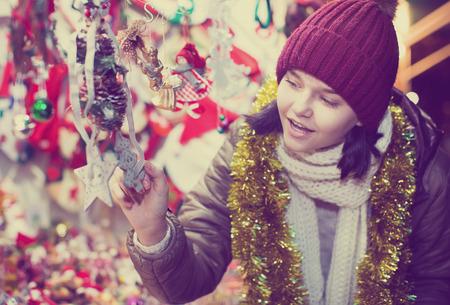 Hübscher Teenager in der Nähe des Kundenzählers mit Weihnachtsdekoration Standard-Bild - 81345747