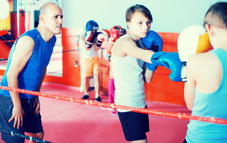 Teenage sportsman at boxing workout with instructor on boxing ring
