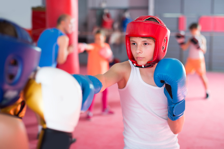 Boys and girl practicing boxing punches with his coach