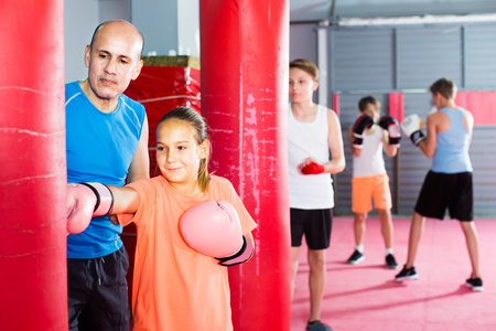 Kids with the help of an instructor are happy to box in training in the hall