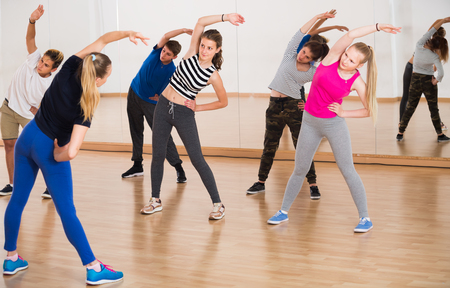 friendly teenage boys and girls learning to dance in dance hall Stock Photo