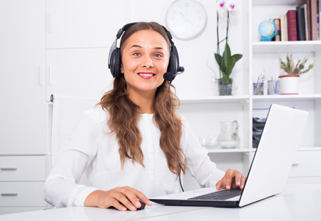 portrait of smiling female operator with headset on answering at call center