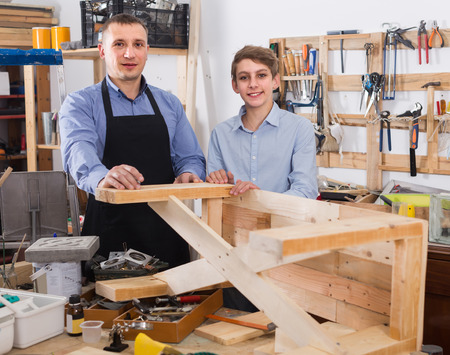 toolroom: smiling father and son chiselling a wooden bench in  workshop Stock Photo