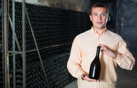 positive male customer holding bottle of red wine from dusty shelves