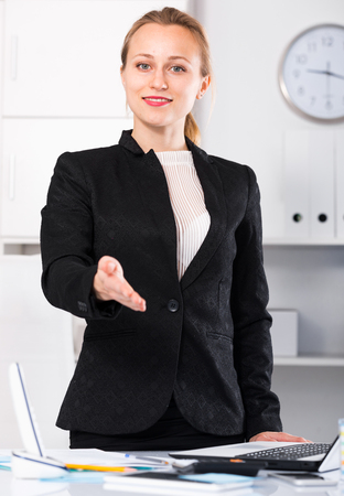 Cheerful businesswoman in suit working in the modern office