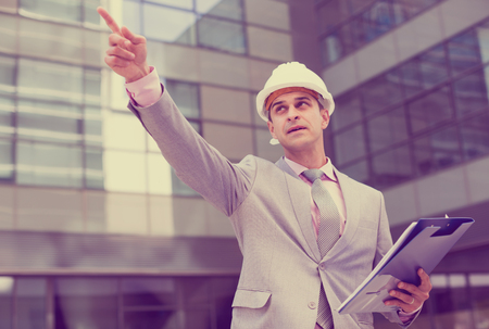 Businessman standing outdoor and pointing at something
