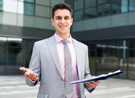 Smiling young businessman presenting factory and welcoming partners Stock Photo