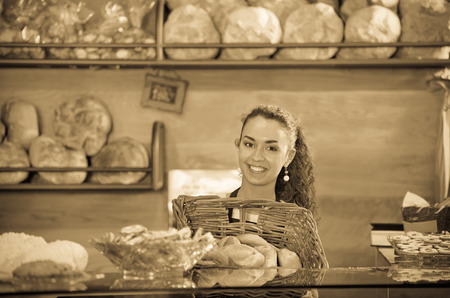Happy shopgirl working in bakery with bread and different pastry Stock Photo