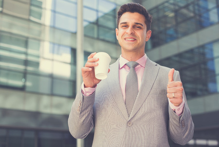 Smiling businessman with cup of coffee showing thumb as sign of success