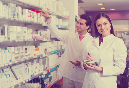 dispensary: Portrait of two friendly smiling pharmacists in uniform working in modern pharmacy