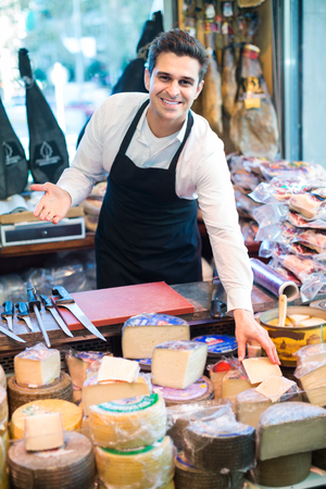 Friendly salesman with different types of cheese in gastronomy Stock Photo