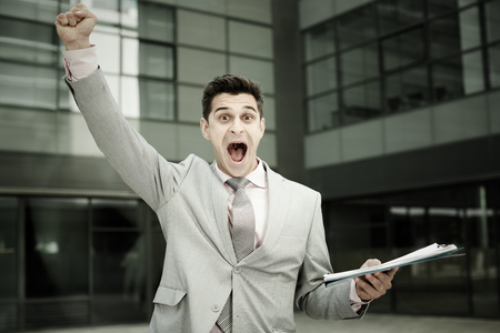Emotional portrait of young businessman outdoor celebrating success with arm raised