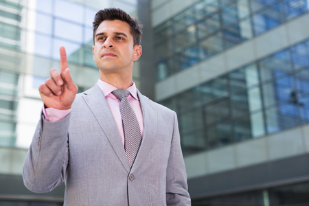 Businessman standing with factory background and touching imaginary virtual screen