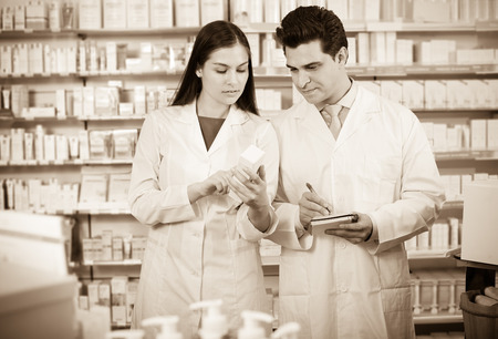 Young happy team of pharmaceutist and technician working in the chemist shop