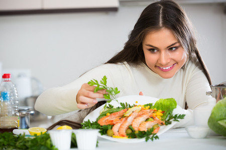 Young brunette in white pullover decorating plate with fried prawns at home kitchen Stock Photo