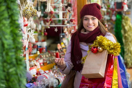 Portrait of happy smiling young brunette choosing Christmas decoration at market