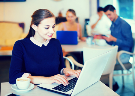 avocation: young woman using laptop and drinking coffee in modern cafe