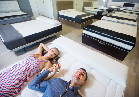 Ordinary family choosing mattresses in the store