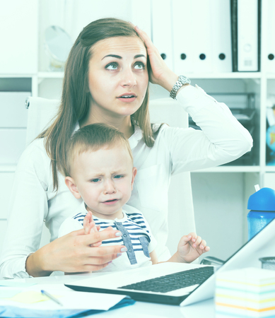 Perplexed mom with child is having issue while working behind laptop in office.