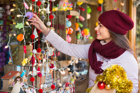 overspending: Cheerful young woman choosing Christmas decoration at market Stock Photo