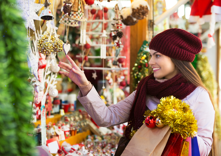 Portrait of young smiling woman shopping at festive fair before Christmas