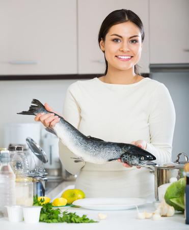 jorobado: Sonriente a mujer joven en suéter blanco limpiando trucha arco iris fresca