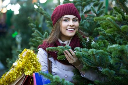 overspending: Portrait of smiling charming girl choosing New Years tree in fair