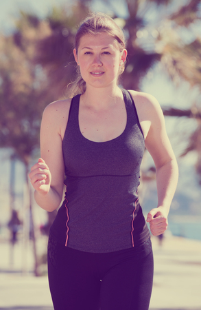 Svelte woman jogging during outdoor workout on city seafront Stock Photo