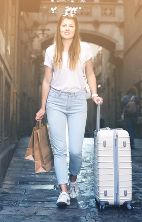 Cheerful young traveling female  walking with luggage in the city on vacation