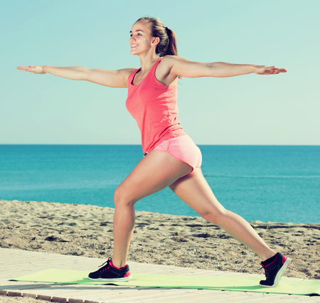 cheerful young female exercising on exercise mat outdoor at the seaside