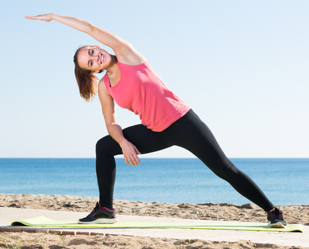 positive girl exercising on exercise mat outdoor at the seaside