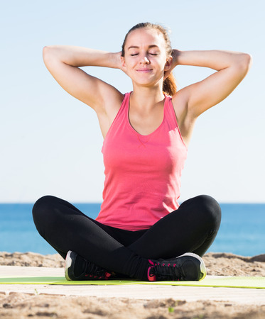 vigorous girl exercising on exercise mat outdoor at the seaside Stock Photo